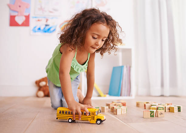 Vroom goes the school bus Shot of a little girl playing with a toy truck and building blocks girl bedroom stock pictures, royalty-free photos & images