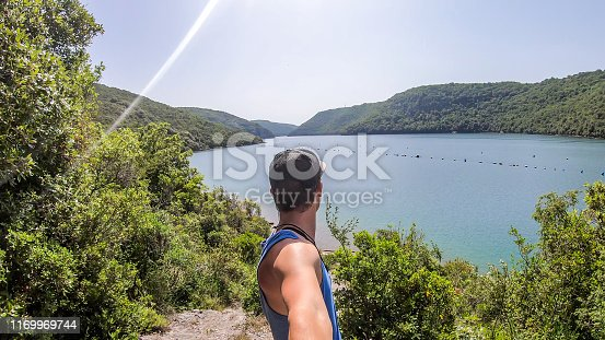 Man taking a selfie with fjord. Boy is looking at the fjord, enjoying the view through the crown of the trees. Steep slopes going down straight to the water. Hills are covered with lush green plants