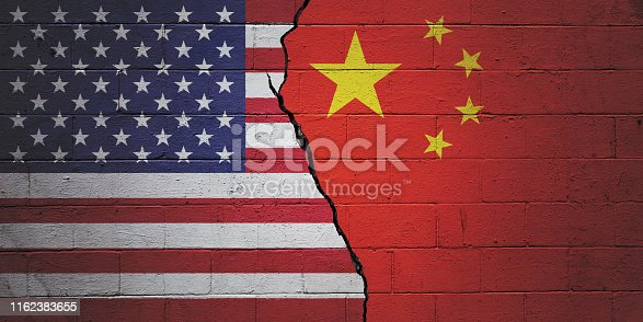 Cracked brick wall painted with an American flag on the left and a Chinese flag on the right.
