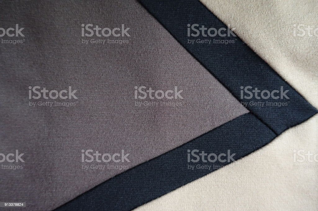 V-shaped black ribbons sewn to grey and beige fabric stock photo
