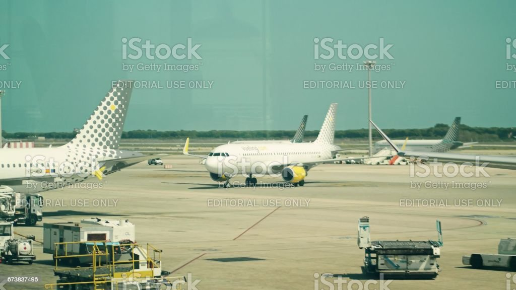 BARCELONA, SPAIN - APRIL, 15, 2017. Vueling Airlines commercial airplanes taxiing and being maintained at El Prat airport royalty-free stock photo