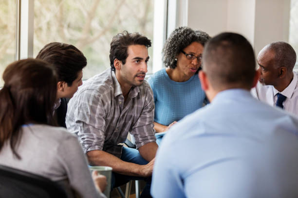 Vulnerable mid adult man talks in group therapy meeting Serious mid adult Indian man discusses an issue during a group therapy session. The group members attentively listen to him. group therapy stock pictures, royalty-free photos & images