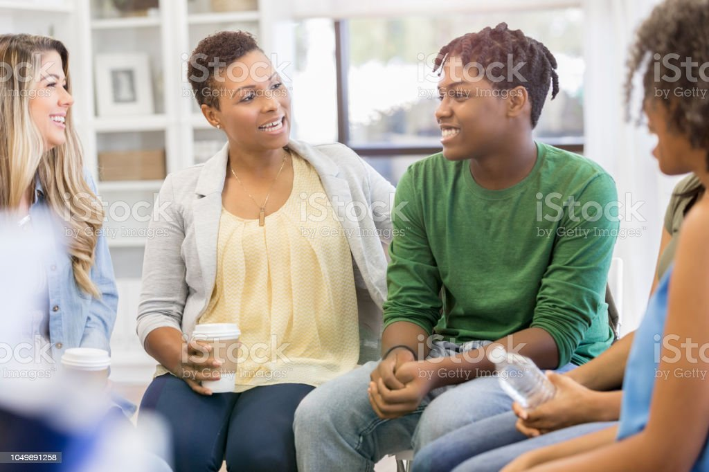 Teenage boy discusses something during a. support group or group...