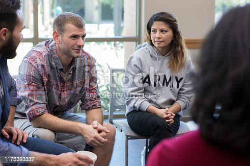 Mid adult male veterans discusses war experiences during a support group meeting for veterans.