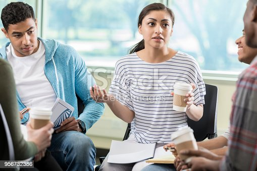 istock Vulnerable woman discusses something in group therapy 956732386