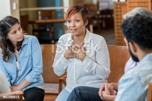 Serious woman discusses something difficult during a support group meeting.
