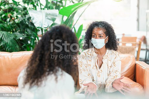 A serious mature woman gestures as she talks with a female mental health professional. The woman is wearing a protective mask as she is meeting with the counselor during the coronavirus crisis.