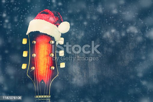 Vulture of electric guitar with Santa Claus Hat on a blue background. New Year's card for the musician. Musical background.