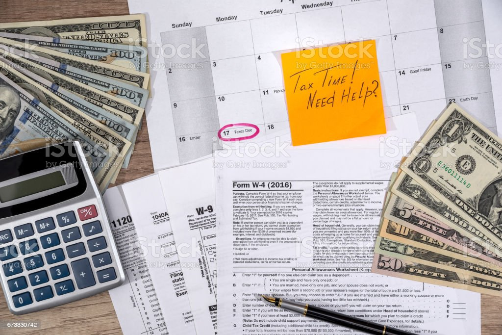 w4, w9 tax form with money on desk. stock photo