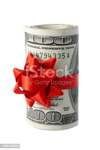 A wad of US one hundred dollar bills wrapped in a red ribbon with a gift bow attached. Shallow depth of field. Focus on the top