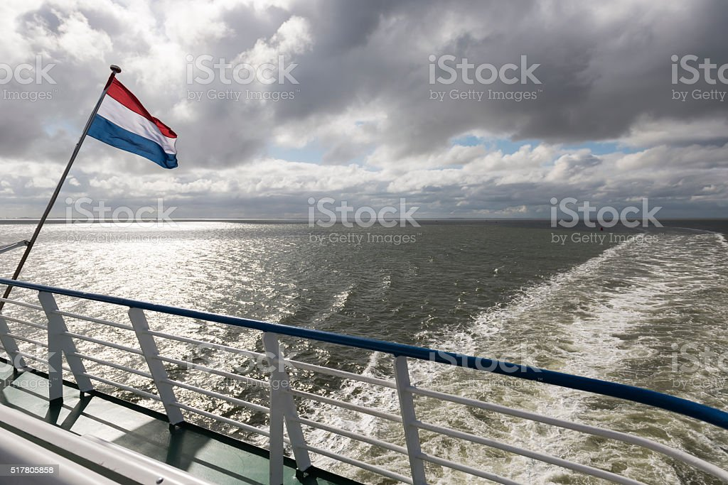 Wadden Sea with Dutch flag. stock photo