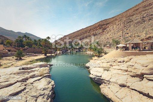 Wadi Bani Khalid, Oman - November 19, 2014: people relaxing at the amazing view of the emerald pools in Wadi Bani Khalid, Oman