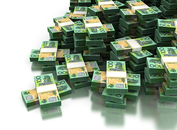 Wads of Australian one hundred dollars piled together stock photo