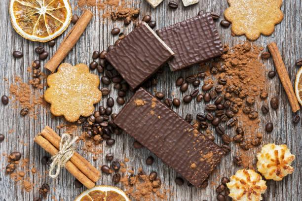 wafer in schokolade mit keksen auf einer hölzernen oberflächen, top sicht. - zimt waffeln stock-fotos und bilder