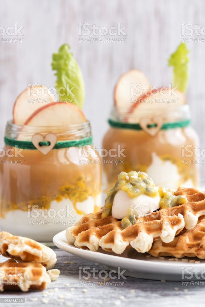 Wafers with cream watered passion fruit. In glass jars, yogurt with apple juice and a green leaf. stock photo