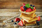 Waffeles with berries and mint leaf on a wood background. toning. selective focus