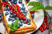 Waffels with cream and berry fruits.