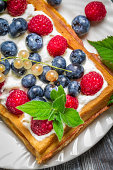 Waffels with cream and blueberry and raspberry.