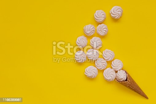 Waffle cone and white twisted meringues on yellow background
