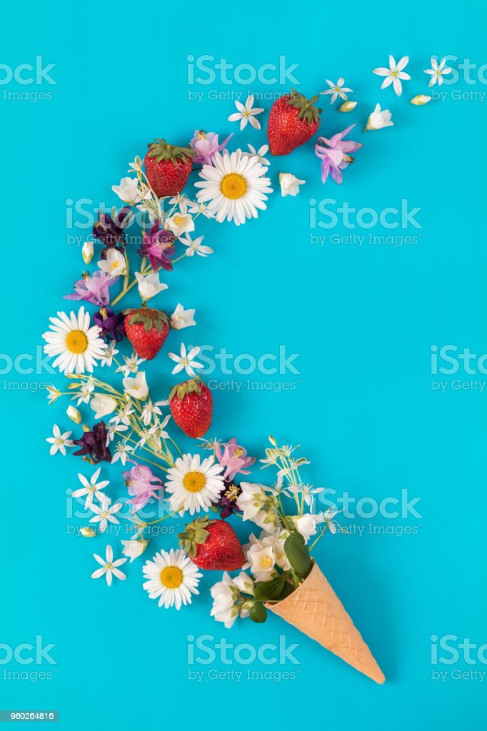 Waffle cone with fresh strawberries and flowers blossom  bouquets on blue surface stock photo