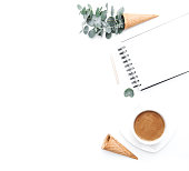 Waffle cone with green leaves eucalyptus and coffee over white background. Femine workspace. Beauty hipster concept