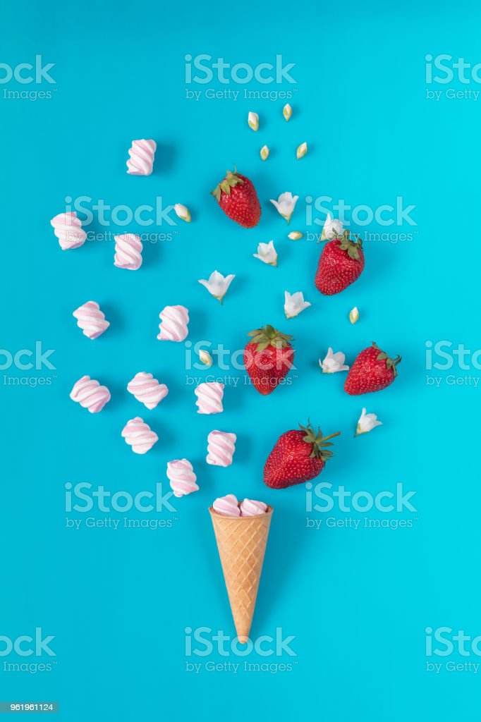 Waffle cone with marshmallows, fresh strawberries and flowers jasmine blossom bouquets stock photo