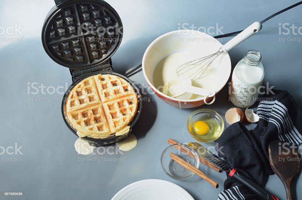 Waffle in open waffle iron, cinnamon grated from cinnamon sticks, stock photo