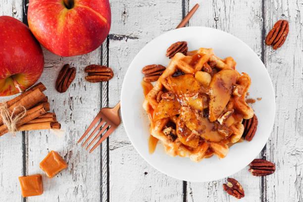 waffel mit gebackenen herbstäpfeln, pekannüssen und karamell, über blick tischszene über einem weißen holzhintergrund - zimt waffeln stock-fotos und bilder