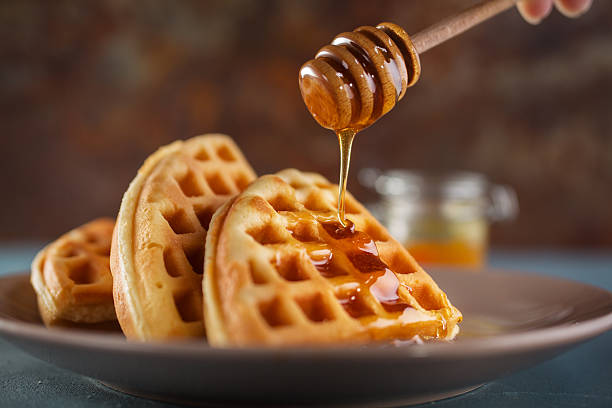 Waffle with honey Honey pouring on a fresh waffles. Breakfast with Belgian waffles waffle stock pictures, royalty-free photos & images