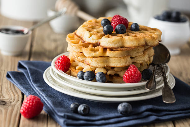 Waffles adorned with blueberries and strawberries on a plate Blueberry waffles with raspberries for breakfast waffle stock pictures, royalty-free photos & images