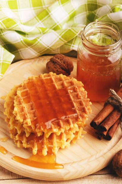 waffles and glass with honey - zimt waffeln stock-fotos und bilder