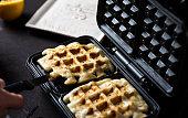 Waffles baking on a waffle maker close up