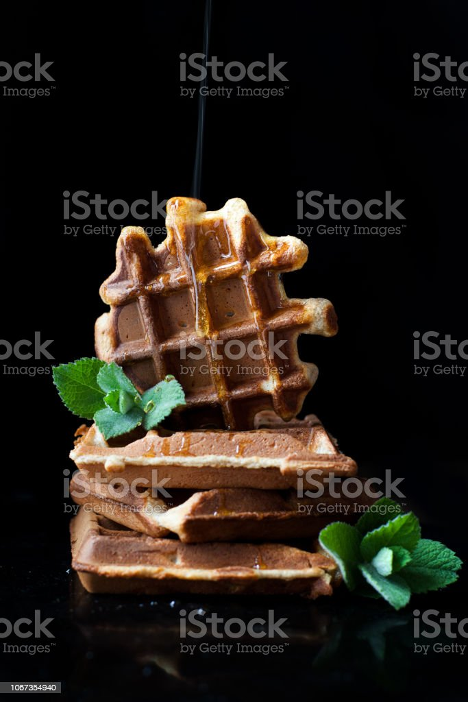 waffles - delicious dessert, breakfast with honey. Photo on a black background. Waffles decorated with mint and sprinkled with honey stock photo