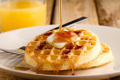 This s a photo of a couple waffles being soaked in syrup. Shot on a wooden table with a shallow depth of field.