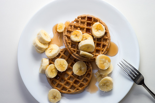Waffle breakfast with bananas and syrup on white plate.