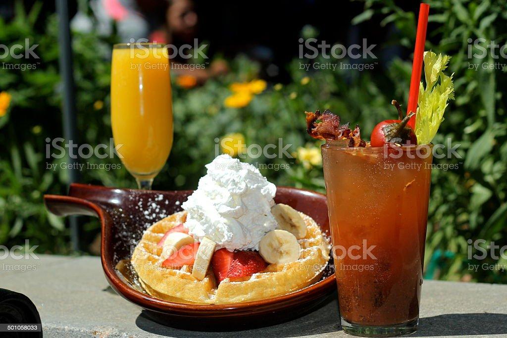 Waffles with Bananas, Strawberries, Whip Cream, Bloody Marys, Mimosas Alfresco stock photo
