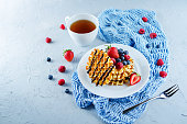 Waffeles with berries and mint leaf and a cup of tea. toning. selective focus