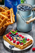 Waffles with berry fruit and whipped cream.