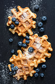 Waffles with blueberries and sugar on slate, top view, vertical composition. Sweet belgian waffles