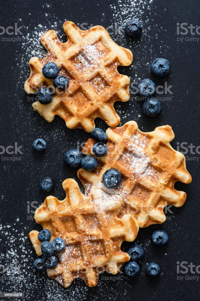 Gaufres aux bleuets et le sucre sur ardoise, top view - Photo