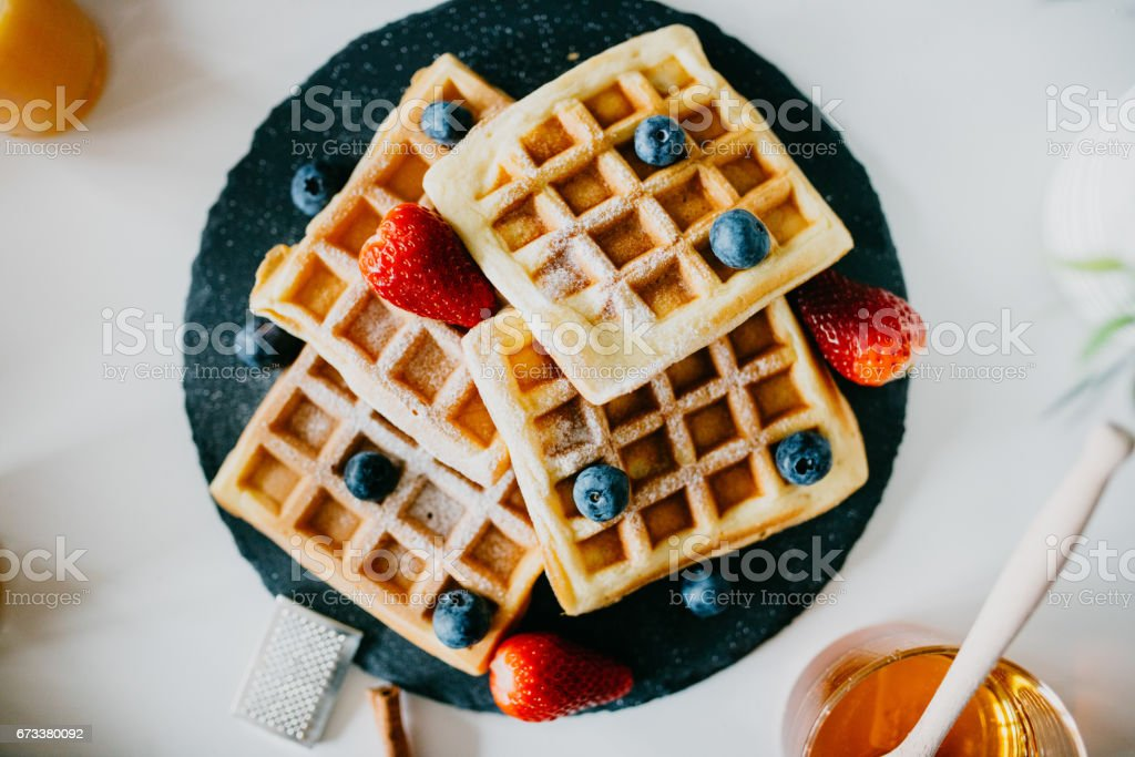 Waffles with blueberries, strawberries and powdered sugar stock photo