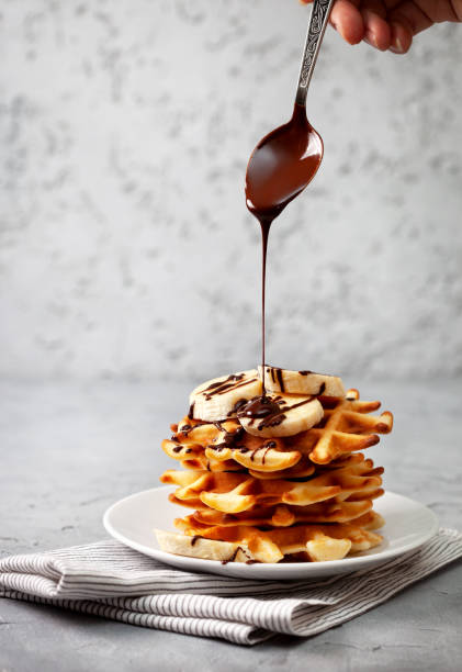 waffles with chocolate sauce belgian waffles with chocolate sauce and banana on a gray concrete background waffle stock pictures, royalty-free photos & images
