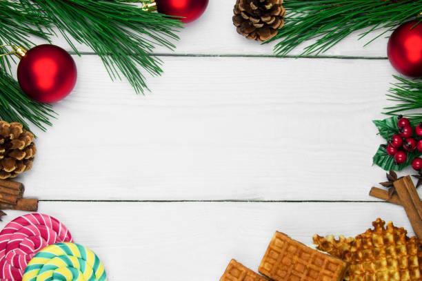 waffeln mit zimt und anis-stars und lutscher. weihnachtsbaum zweig und rote kugel mit konus auf weißem holz vintage-hintergrund - zimt waffeln stock-fotos und bilder