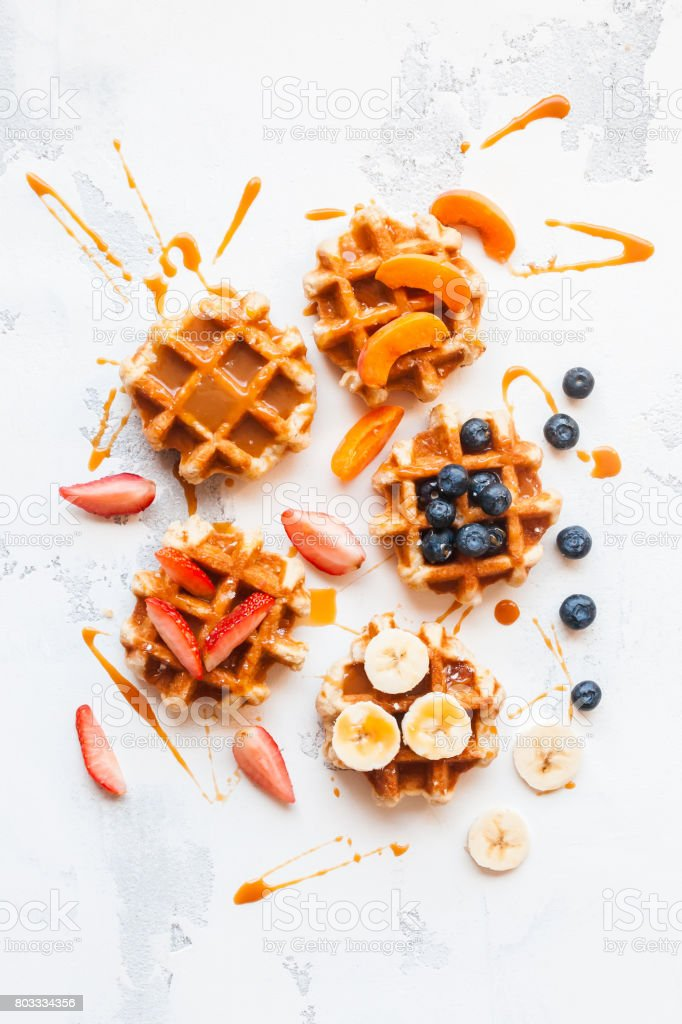 Waffles with fresh fruit and caramel. Flat lay, top view stock photo