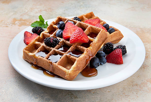 Waffles With Fruit and Maple Syrup on a Marble Counter. A plate of belgian waffles with fruit on a marble counter. waffle stock pictures, royalty-free photos & images