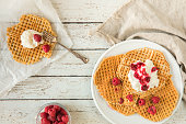 Waffles with raspberries and cream seen from above on a wooden table, flat lay perspecitve. There is a glass bowl with whole raspberries on the table, a fork and a linen cloth.