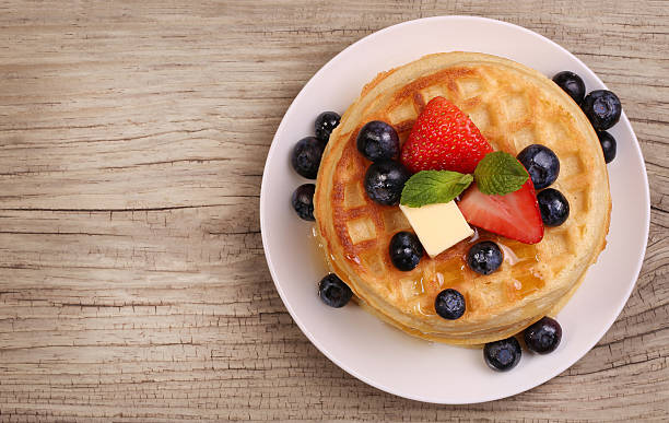 Waffles with Strawberry and Blueberry over wooden background Waffles with Strawberry and Blueberry over wood background waffle stock pictures, royalty-free photos & images
