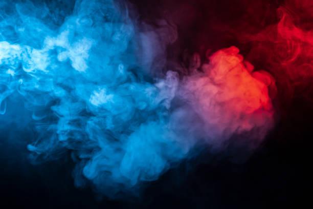 孤立的有色煙霧晶片: 藍色、紅色、橙色、粉紅色;在黑暗中的黑色背景上滾動關閉。圖像檔