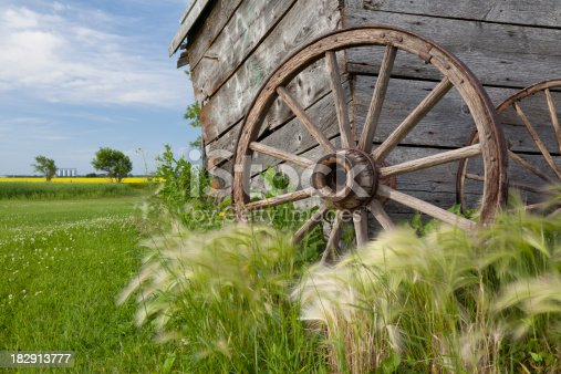Pair of old wagon wheels up against a abandoned farm house on the canadian prairies.