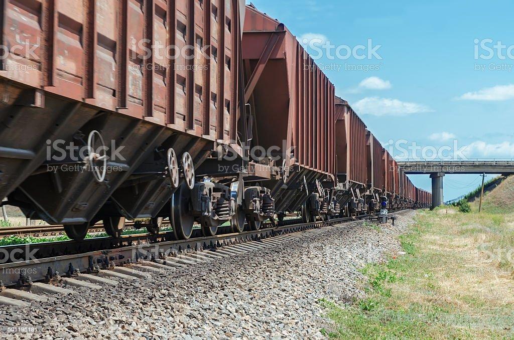 wagons of a freight train go to horizon under bridge stock photo